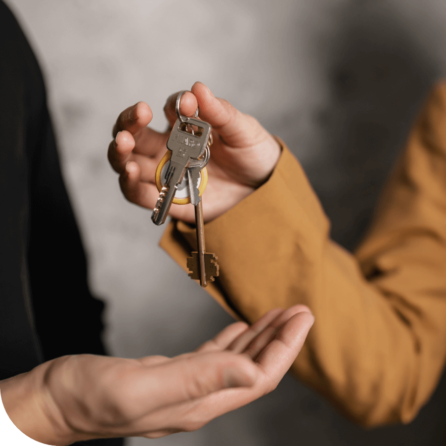 Image of a hand dropping keys to another hand